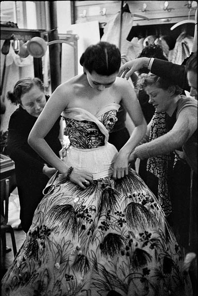 - Henri Cartier-Bresson, Model Alla having theMay dress fitted before thefashion show, 1953. <br>©Henri Cartier-Bresson / Magnum Photos.