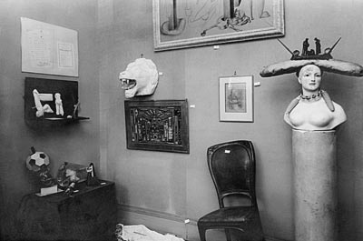 """- Man Ray, view fromthe """"Surrealist Exhibition: Sculptures, Objects, Paintings, Drawings"""" atthe Galerie Pierre Colle, June 1933. <br>© Man Ray Trust / Adagp,  Paris, 2017. <br>Salvador Dalí, Retrospective Bust ofa Woman and Atmospheric Chair, 1933.<br>© Salvador Dalí, Fundació Gala-Salvador Dalí / Adagp, Paris, 2017."""