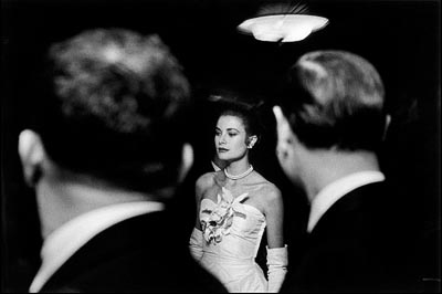 - Elliott Erwitt, Grace Kelly wearing a white satin Dior dress at a ball celebrating her engagement with Prince Rainier of Monaco at the Waldorf Astoria Hotel in New York, January 6, 1956. <br>© Elliott Erwitt / Magnum Photos.