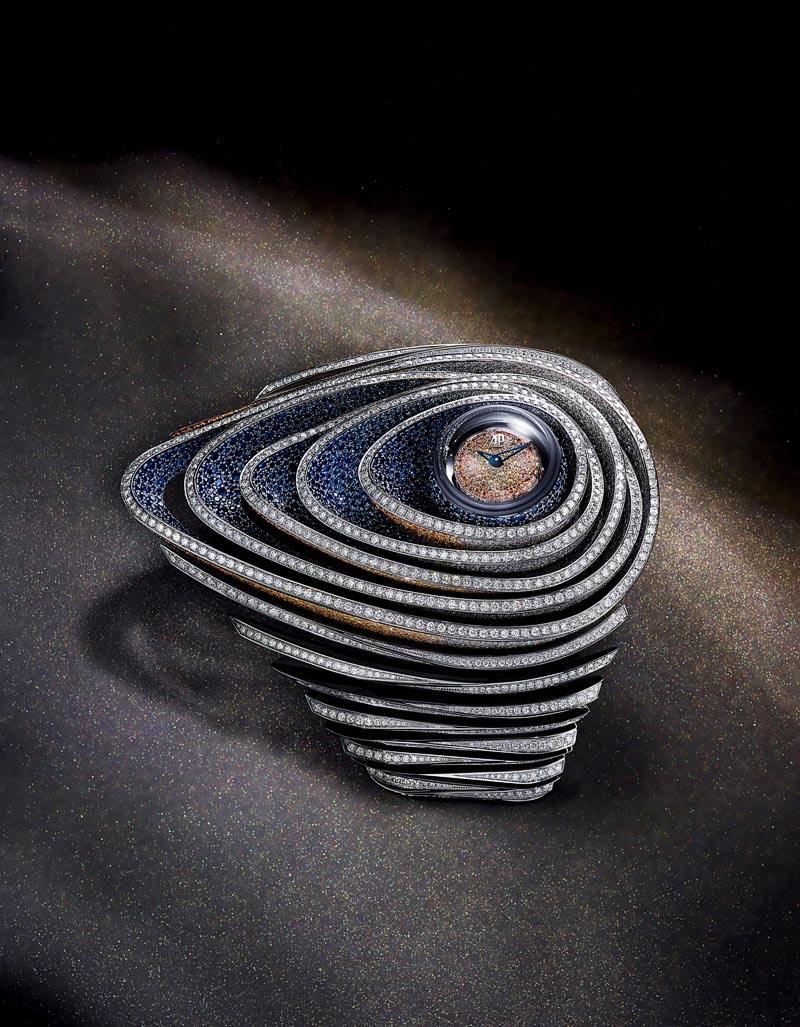 - This piece combines awide array ofdiamonds and sapphires inorange and blue hues