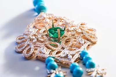 Necklace inpink gold set with1 cushion-cut emerald – Adjusting thecentral emerald on thegem-set motif. Ref.: G37M6900
