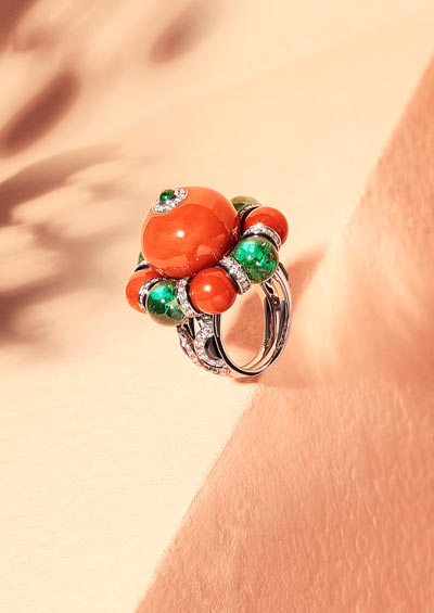 Flamboyant ring: Platinum, one 30.19-carat coral bead, four coral beads totalling 13.47 carats, four emerald beads fromZambia totalling 14.28 carats, cabochon-cut emerald, onyx, black lacquer, brilliant-cut diamonds.
