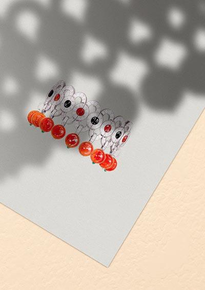 Flamboyant bracelet: Platinum, fourteen coral beads totalling 133.68 carats, coral, onyx, round-cut emeralds, brilliant-cut diamonds.
